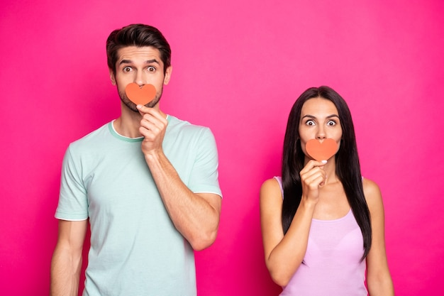 Photo of cute guy and lady holding little paper hearts in hands hiding mouth keeping silence wear casual outfit isolated pink color background
