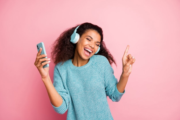 Photo of cute nice casual sweet casual stylish trendy woman wearing blue sweater curly wavy brown haited with eyes closed holding telephone dancing isolated pastel color wall