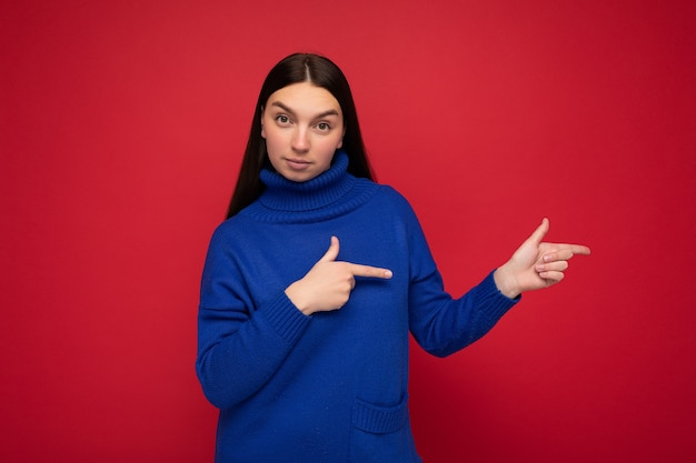 Photo of cute nice winsome adult woman wearing casual outfit isolated on background wall with copy space pointing at free space with hands.