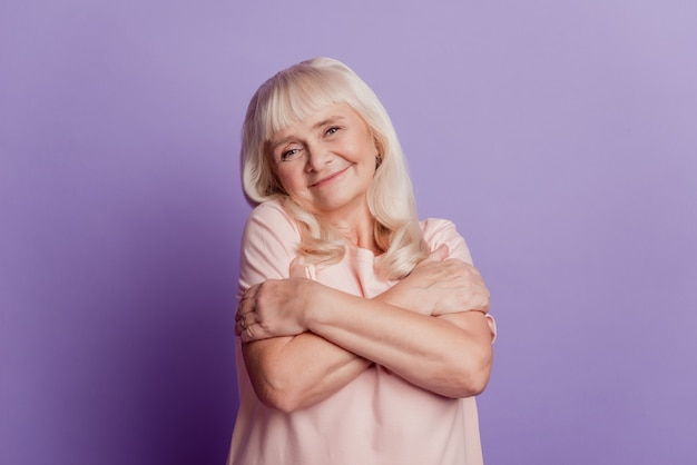 Photo of cute old lady embracing herself isolated on purple background