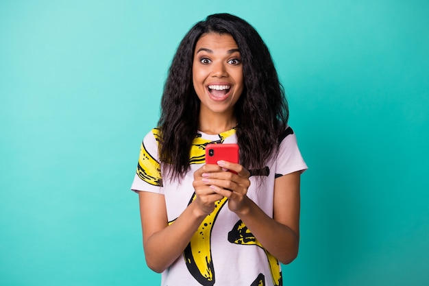 Photo of cute young lady hold smartphone open mouth wear banana print t-shirt isolated turquoise color background