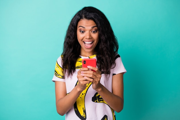 Photo of cute young lady hold telephone look screen open mouth wear banana print t-shirt isolated teal color background