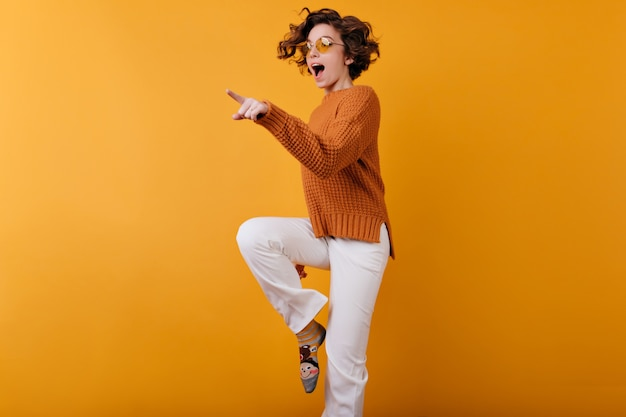 Photo of dark-haired girl in woolen sweater dancing on orange space with smile