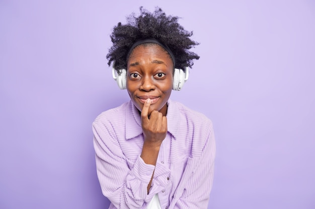 Photo of dark skinned curly haired woman with curious expression keeps finger on lips enjoys listening favorite music via headphones