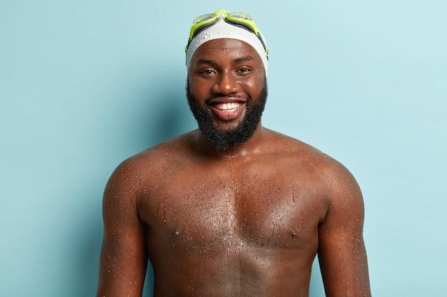 La foto del maschio afro felice dalla pelle scura ha un ampio sorriso, denti bianchi perfetti, posa nuda su sfondo blu