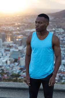 Photo of dark skinned motivated athletic man with muscles, has regular training in open air, thinks about new challenge, wears blue t shirt and black leggings, stands against city view with sunshine.