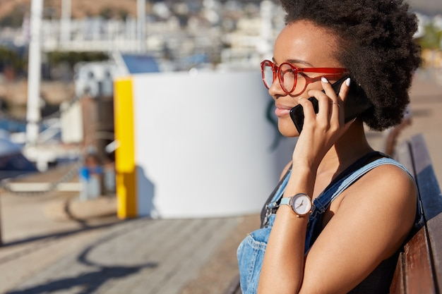 Photo of dark skinned woman in eyewear, has phone conversation with boyfriend, dressed casually, has watch at wrist, focused into distance, enjoys spare time. street style, technology concept