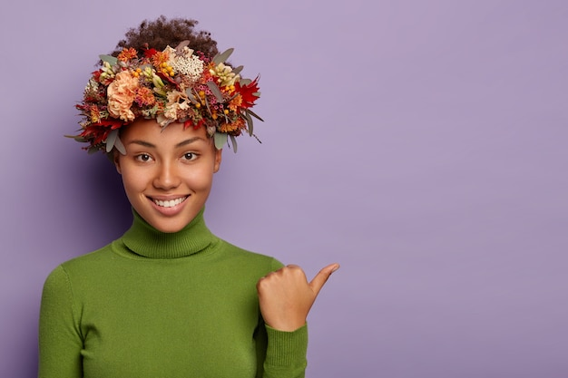 Photo of dark skinned young curly woman points thumb away, wears green turtleneck, autumnal wreath, has pleasant smile, demonstrates copy space for your advertising content, gives suggestion