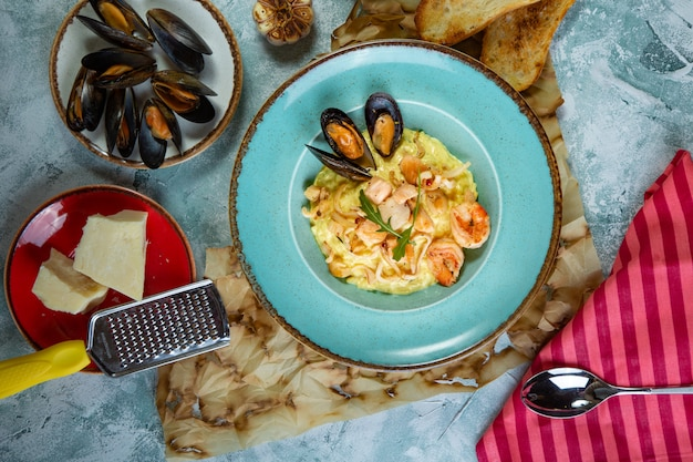 Photo of delicious risotto with saffron and seafood on table.