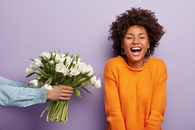 Photo of delighted african american lady laughs sincerely, gets flowers from husband or boyfriend