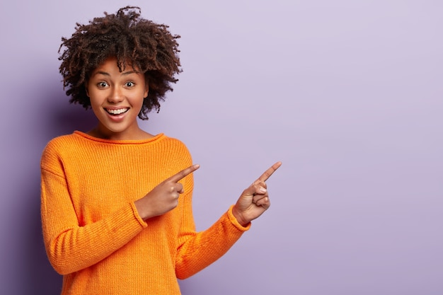 Photo of delighted african american woman points away with both index fingers, promots awesome place for your advertising content