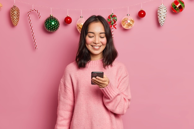 Photo of delighted brunette asian woman with eastern appearance holds modern mobile phone sends messages of congratulation on new years eve wears casual jumper poses