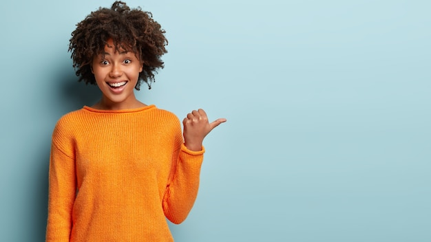 Photo of delighted cheerful afro american woman with crisp hair, points away, shows blank space, happy to advertise item on sale, wears orange jumper, demonstrates where clothes shop situated