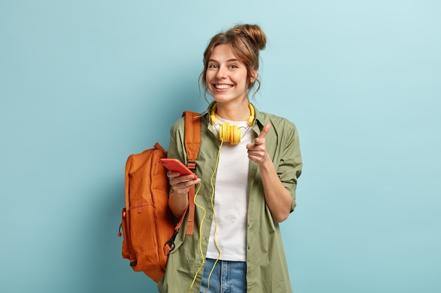 Photo of delighted european woman points at you happily, holds smartphone device connected to headphones, uses music app