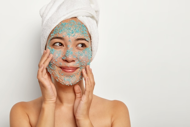 Photo of delighted female model stands topless against white wall, touches face skin, makes peeling with sea salt scrub, removes pores and white spots. skin solution and spa treatment concept