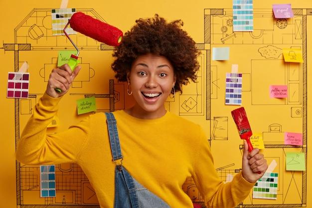 Foto di una donna felice con i capelli ricci, tiene il rullo di vernice e il pennello, solleva le braccia con strumenti di riparazione