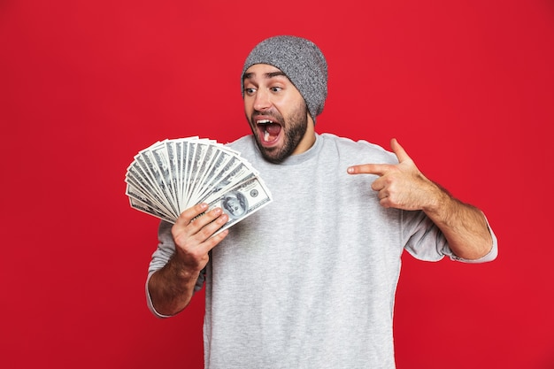 Photo of delighted guy 30s in casual wear rejoicing and holding cash money isolated