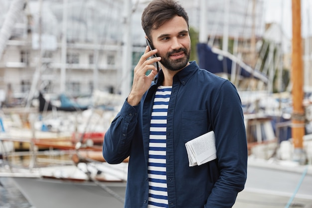 Photo of delighted hipster guy with dark beard has telephone coversation, strolls near bay in harbour, carries newspaper, looks aside