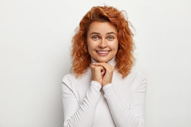Foto della signora sorridente felice con i capelli ondulati dello zenzero