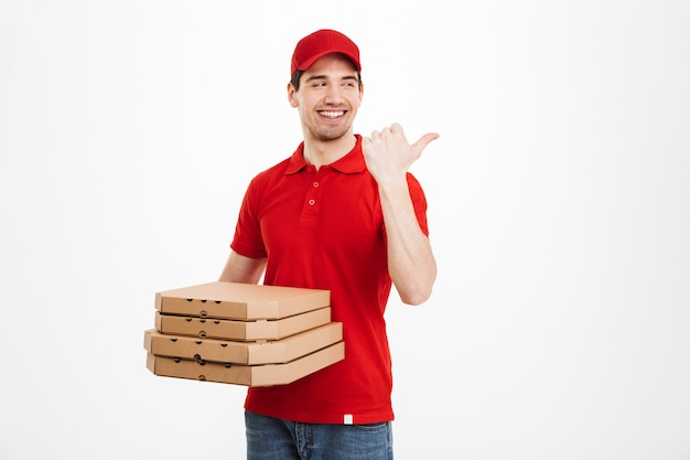 Photo of delivery dealer 25y in red uniform carrying stack of pizza boxes and pointing finger aside on copyspace, isolated over white space