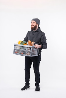 Photo of a delivery man holding a box with some groceries in it and smiling is looking at someone