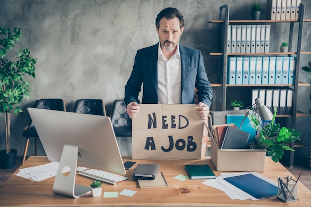 Photo of despair sad layoff dismissed worker mature jobless guy hold placard poster search job world crisis ruined career workplace fired packing stuff modern office desktop table indoors