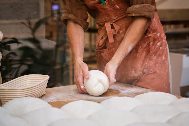 Фото детали руки пекаря, работающего с тестом для хлеба