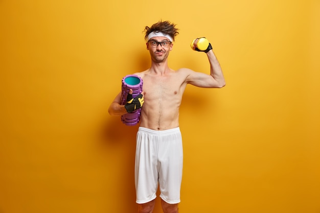 Photo of determined athletic man lifts dumbbell, poses with foam roller, has aim to be strong, enjoys exercises in gym, isolated on yellow wall. people, health and fitness concept. healthy lifestyle