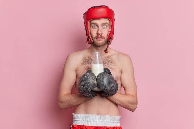La foto di un determinato pugile maschio ha l'obiettivo di vincere la partita prepararsi per la lotta indossa guanti da boxe e casco protettivo beve latte poiché la fonte di calcio è a torso nudo.