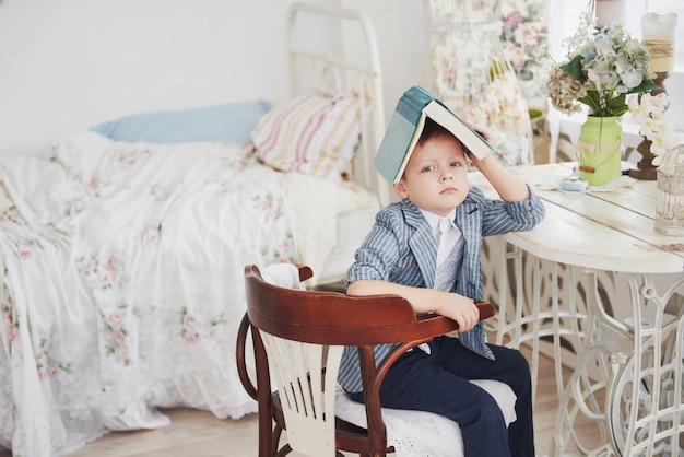 Photo of diligent schoolboy with book on his head does not want to study and go to school