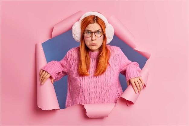 La foto di una femmina di zenzero frustrata delusa porta le labbra e sembra tristemente insoddisfatta mentre sente parole offensive indossa un maglione lavorato a maglia con paraorecchie caldi.