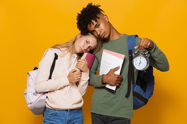 Photo of disappointed students man and woman 16-18 wearing backpacks holding exercise books and alarm clock, isolated over yellow background