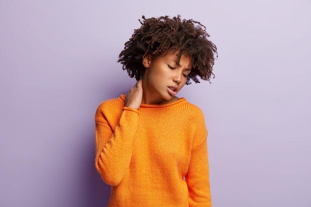 La foto di una donna riccia e scontenta tiene la mano sul collo, soffre di dolori terribili, lavora sodo, ha uno stile di vita sedentario, folti capelli ricci e scuri, indossa un maglione arancione, modelle sul muro viola.