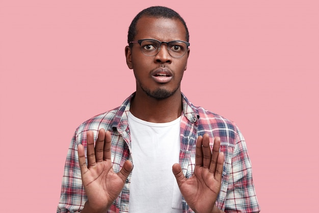 Photo of discontent dark skinned male with displeased expression, makes refusal gesture, asks to stop it. handsome african american man in spectacles gestures