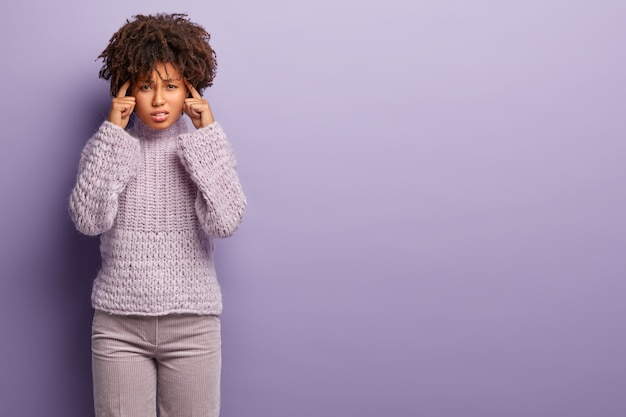 Foto di scontento donna dalla pelle scura tiene le mani sulle tempie, soffre di emicrania, sentimenti dolorosi, indossa maglione e pantaloni lavorati a maglia, cerca di concentrarsi su qualcosa. spazio libero per il testo