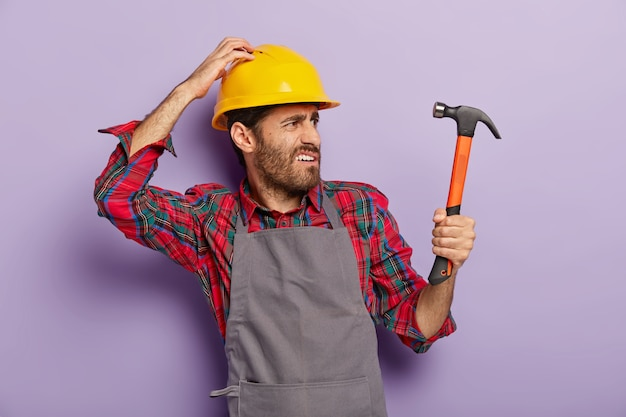 Photo of discontent handyman turns right, looks into distance with frowned face, holds hammer, being professional builder, notices new object for repairing wears helmet, apron. renovation, engineering