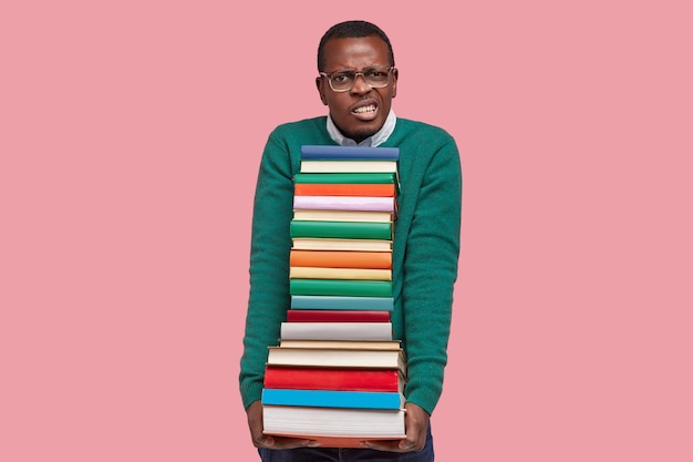 Photo of discontent nerd clenches teeth, holds pile of textbooks, wears big spectacles and green sweater