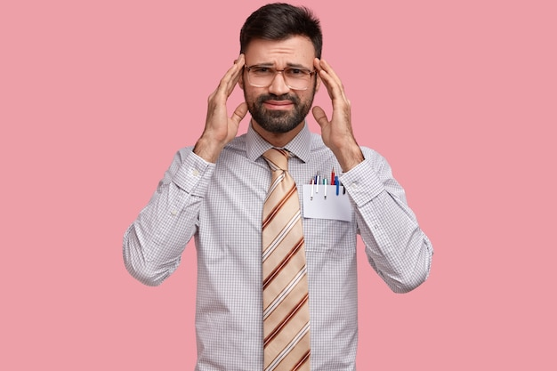 Foto di malcontento uomo con la barba lunga soffre di mal di testa, tiene le mani sulle tempie, ha un'espressione triste, stanco dopo il lavoro in ufficio