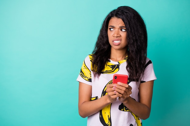 Photo of disgusted displeased girl hold phone look empty space wear banana print t-shirt isolated turquoise color background