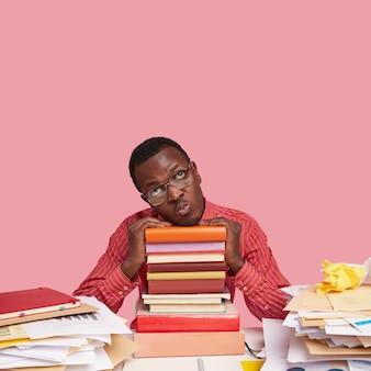 Foto di uno studente afroamericano dispiaciuto con espressione cupa, tiene le mani su una pila di libri di testo, inclina la testa, vestito con una camicia rosa