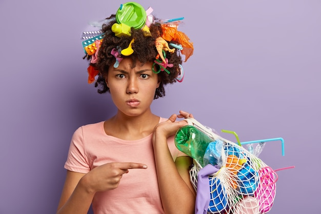 Photo of displeased afro american woman angry with abusive use of plastic, points at bag with collected garbage, has wastes in head, isolated on purple wall. non recyclable pollution concept