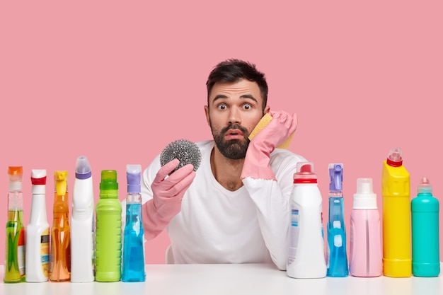 Photo of displeased bearded man in rubber protective gloves holds rag for cleaning kitchen stove, looks embarrassed