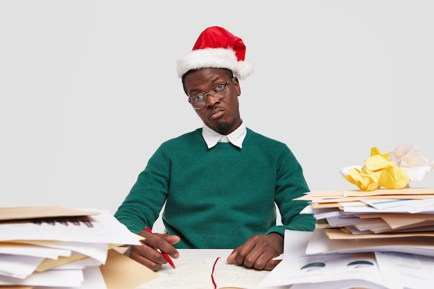 Photo of displeased black man feels apathy as doesnt want to work, dressed in festive headgear and sweater, surrounded with piles of documents
