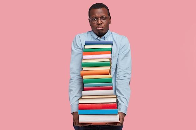 La foto di un uomo di colore scontento ha un'espressione facciale infelice, trasporta un enorme mucchio di letteratura