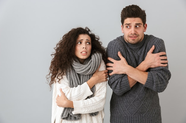 Photo of displeased couple man and woman wearing scarfs trembling and hugging themselves, isolated over gray wall