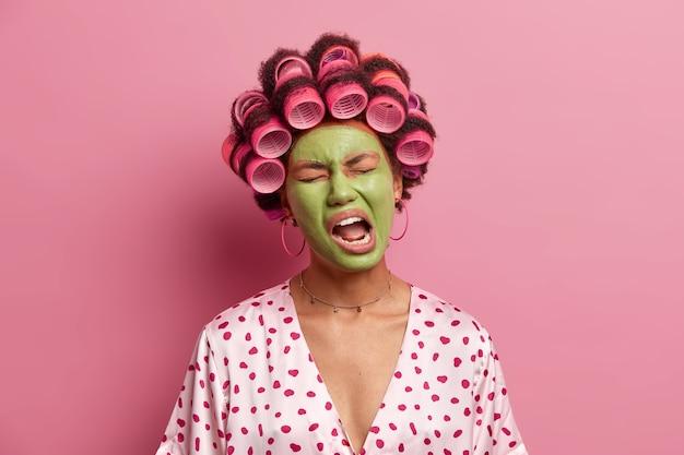 La foto della donna etnica scontenta tiene la bocca aperta, sente la stanchezza, sbadiglia e applica una maschera verde, vestita con abiti domestici casual, isolata sul rosa. trattamento viso e concetto di benessere