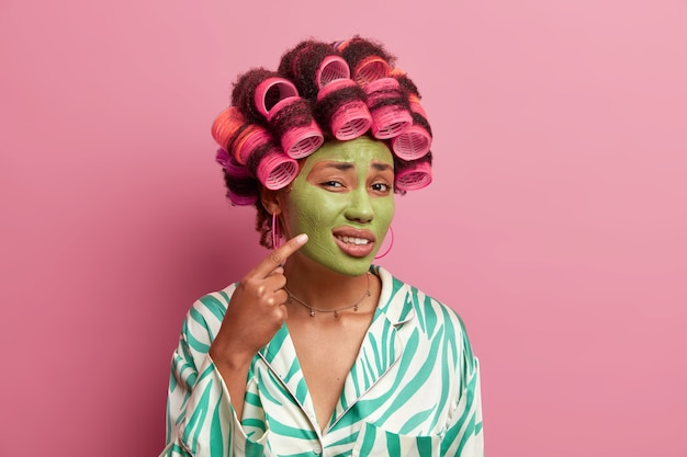 Photo of displeased ethnic woman points at problematic zone on face, indicates at cheek and shows pimple, wears green moisturizing face mask, applies hair rollers, wears casual dressing gown. beauty