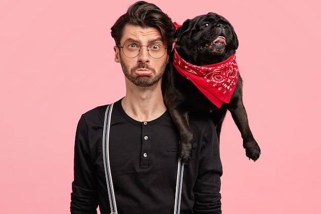 Photo of displeased male owner of pedigree black dog, spend free time at home, isolated over pink wall. funny pet with red bandana on host`s shoulder. animals, family, relationship concept