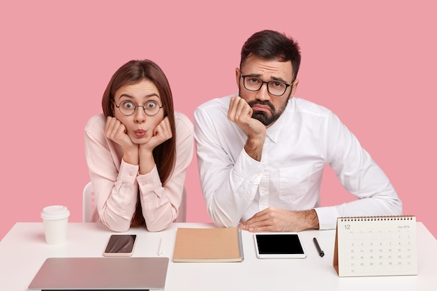 Photo of displeased office worker and his female partner look surprisingly and sadly, tired of working, use modern gadgets, pose at workplace, drink takeaway coffee, isolated over pink wall