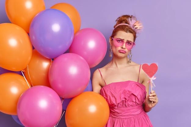 La foto della giovane donna dispiaciuta della testarossa guarda con l'espressione cupa alla macchina fotografica tiene i palloncini multicolori della caramella deliziosi pone interna contro fondo viola